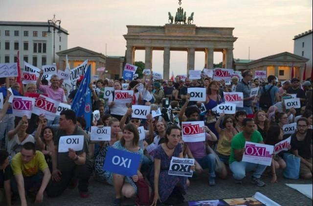 Foto von Demonstrantinnen gestern in Berlin vor dem Brandenburger Tor, die trotz Hetze OXI-Schilder hoch halten